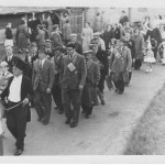 Men marching past Riverside
