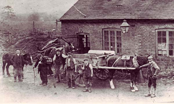 On the left, the Forge c 1909. Master blacksmith Jim Hobbs (fourth from left) is flanked by his sons Donald and Harold. Employee Walter Lambert holds the pony (extreme left) and the little old man, Jimmie Lock, retired and blind, carries a travelling blacksmith's travelling toolbox. Right, the Forge with Forge Cottage.